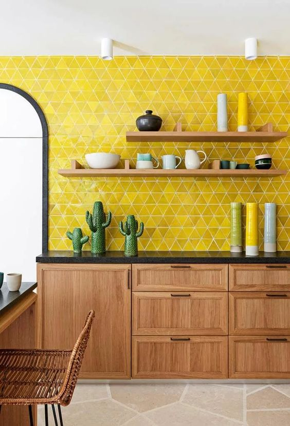 a light-stained kitchen with black countertops, open shelves and a super bold yellow triangle backsplash and bold accessories