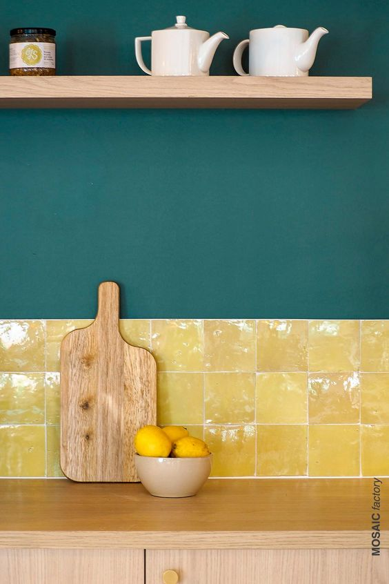 a light-stained kitchen with dark green walls and a bold and shiny yellow tile backsplash plus an open shelf is a lovely idea