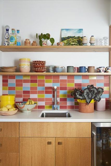 a light-stained modern kitchen with white stone countertops and a colorful tile backsplash in pink, red, blue and yellow that creates a mood in the space