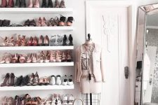 a lovely and glam feminine closet with open shelves, a grey storage pouf, a large mirror and touches of blush pink