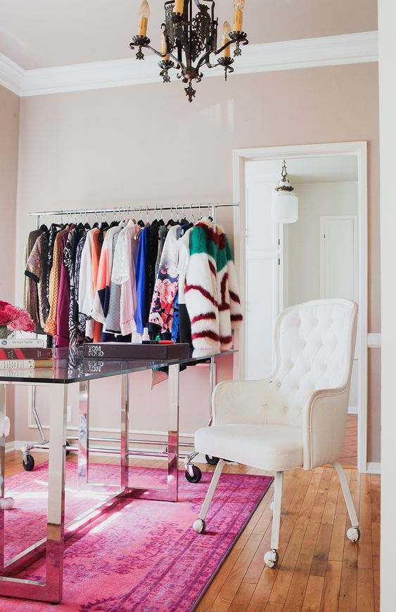 a lovely cloffice with a makeshiift closet, a large mirror, a glass desk, a white chair on casters and a black chandelier