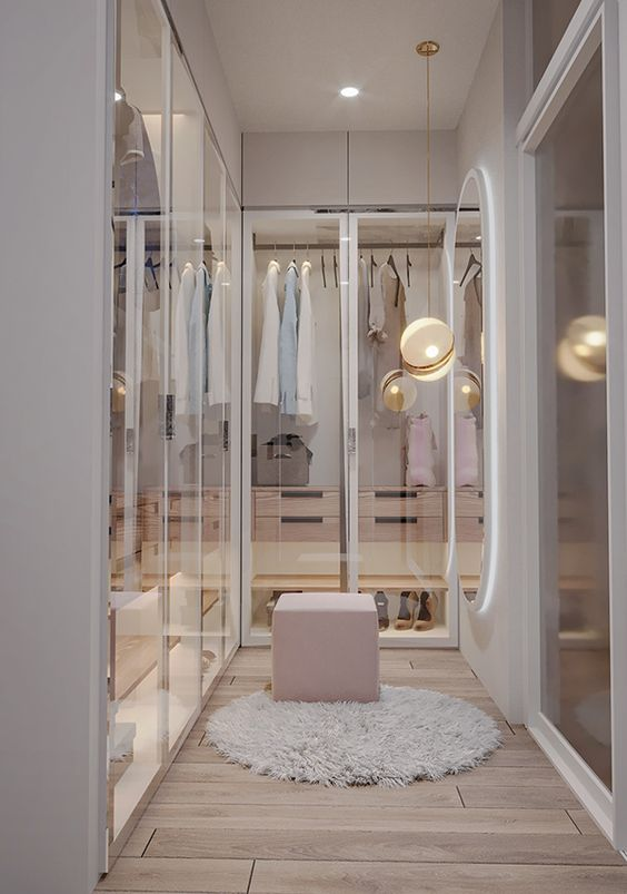 a lovely contemporary girlish closet a lit up wardrobe and glass doors and small cabinets with drawers built inside and a pink pouf