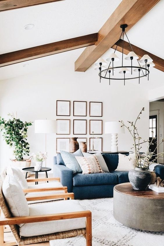 a lovely contemporary living room with wooden beams, a blue sofa, white chairs, a round coffee table, a chic chandelier and a potted plant