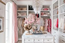 a lovely glam girlish closet with open storage units, drawers, a large cabient with drawers for accessories, a crystal chandelier, a printed rug