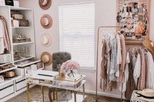 a lovely pink closet with open storage units and drawers, a makeshift clsoet, a crystal chandelier, a mini desk and a grey chair plus hats as decor