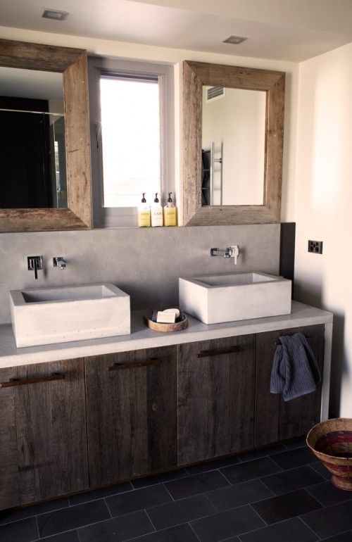 a minimalist barn bathroom with concrete walls, a weathered wood vanity, concrete sinks and mirrors in wooden frames
