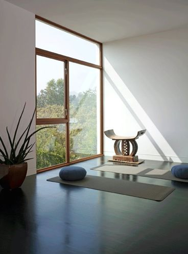 a minimalist meditation room with a large window for views and some mats and cushions