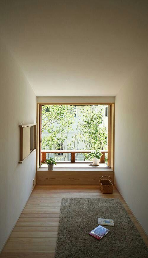 a minimalist meditation space with a rug, some potted greenery, baskets and a window with greenery