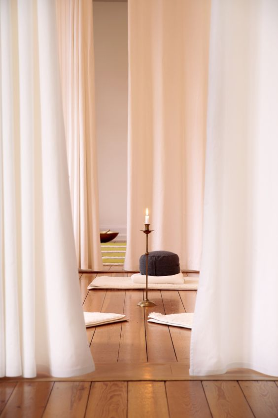 a minimalist meditation space with curtains, rugs, pillows and candles in candle holders