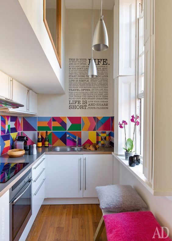 a modern white kitchen with grey countertops, a colorful tile backsplash, pendant lamps and colorful stools is a lovely idea