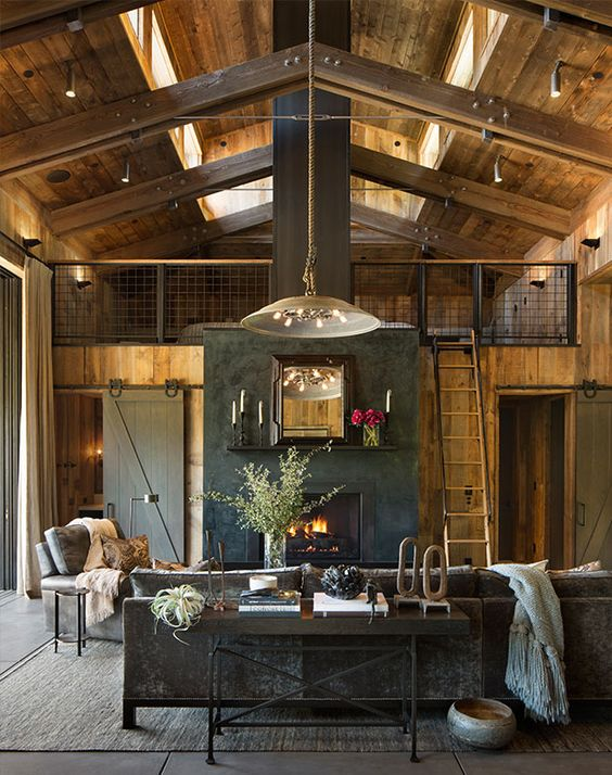 a moody barn living room with wooden walls and a ceiling, grey seating furniture, neutral textiles, pendant lamps, a built-in fireplace