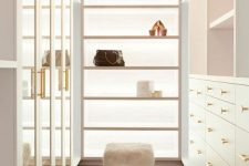 a neutral and very chic closet with drawers with glass doors, open shelves and drawers, open shelves and faux fur stools plus a crystal chandelier