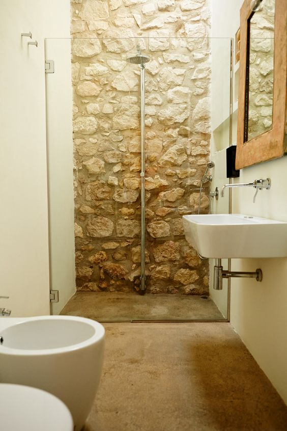 a neutral barn bathroom with a stone wall in the shower, a stone floor and modern appliances looks contrasting