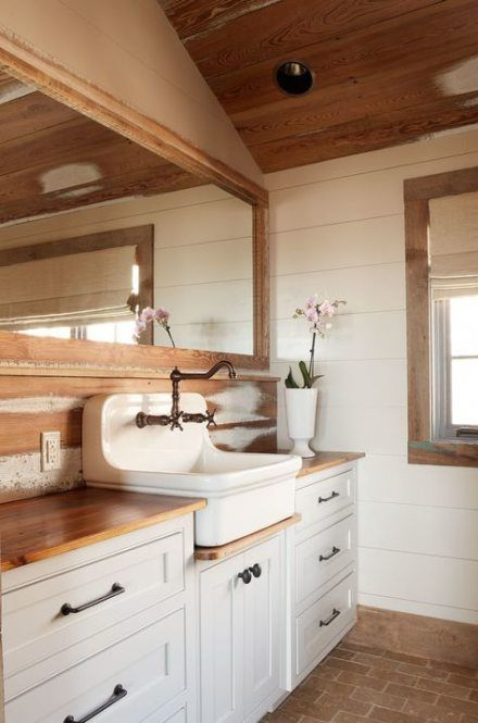 a neutral barn bathroom with wooden plank walls, a staiend ceiling, a white vanity and a vintage sink plus a large mirror