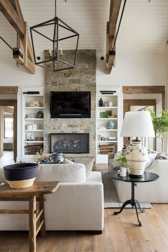 a neutral barn living room with a built-in fireplace, neutral seating furniture, wooden beams, a metal chandelier and baskets