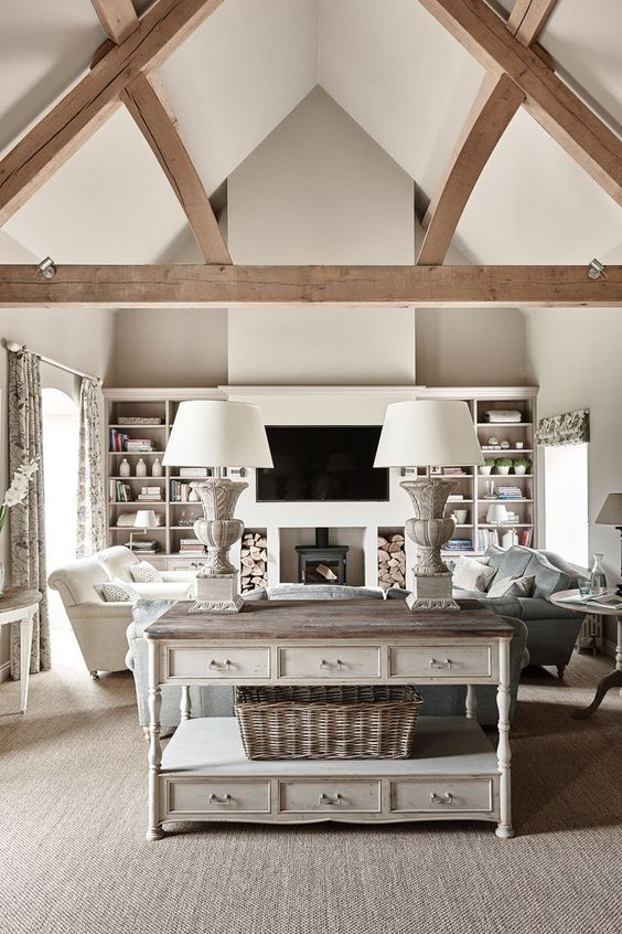 a neutral barn living room with a metal hearth, built-in shelves, neutral and pastel seating furniture, a whitewashed console table, wooden beams