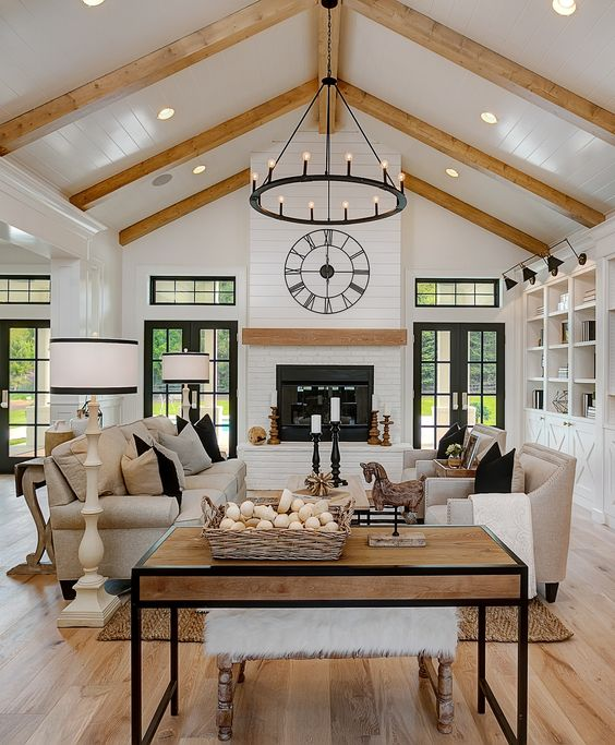 a neutral barn living room with white planked walls and a ceiling, wooden beams, a fireplace, neutral seating furniture, coffee tables and a metal chandelier