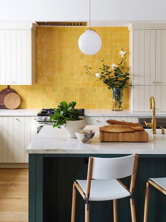 a neutral planked kitchen with a teal kitchen island and white stone countertops, a bold yellow tile backsplash is a very pretty idea