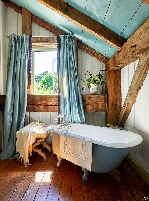 a pretty barn bathroom with wooden plank walls, a floor and ceiling, wooden beams, a blue clawfoot tub and blue curtains on the window