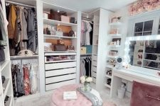 a pretty glam feminine closet with open storage units and drawers, a pink pouf and rug, a white vanity and a pink chair