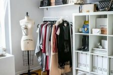 a pretty neutral closet with a makeshirt part, open storage shelves, a tufted bench, hats as decor and a printed rug is amazing