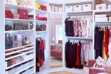 a prety and glam feminine walk-in closet with open storage units, boxes for storage, a full size mirror, a pink chair and a rug