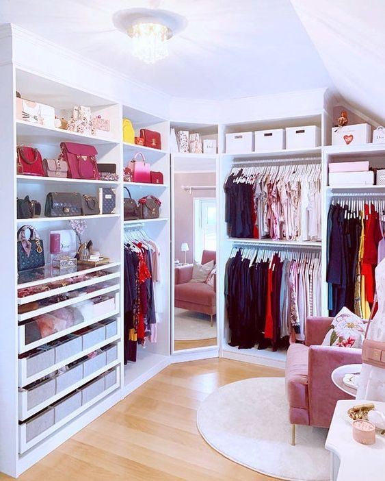 a prety and glam feminine walk in closet with open storage units, boxes for storage, a full size mirror, a pink chair and a rug