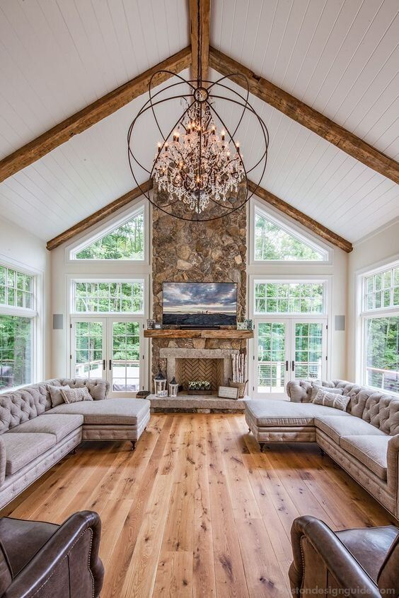a refined barn living room with a fireplace clad with stone, grey vintage sectionals, leather chairs, a sphere crystal chandelier