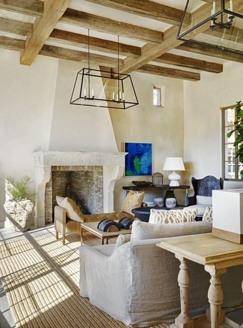 a refined barn living room with wooden beams, a fireplace clad with brick, neutral seating furniture, metal chandeliers and blue touches