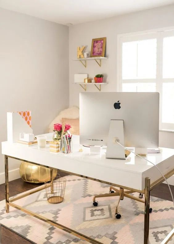 a refined feminine home office with a printed rug, neutral furniture, open shelves and touches of gold