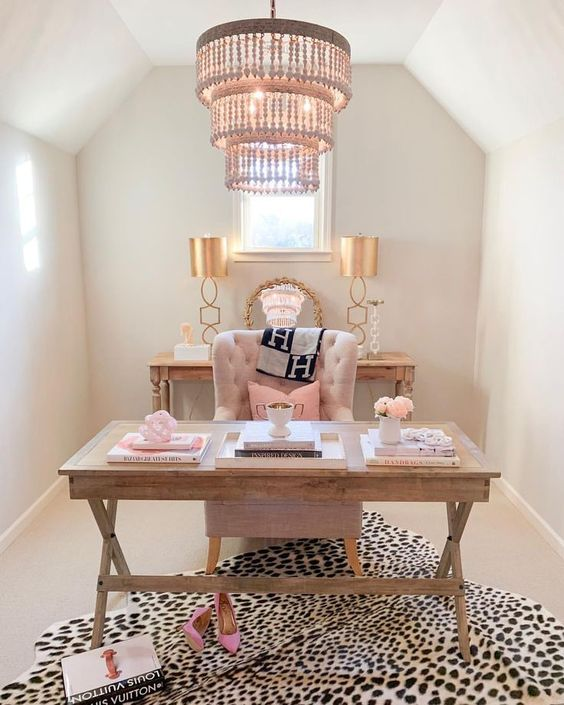 a refined feminine home office with wooden furniture, pink pillows, a printed rug and a statement chandelier