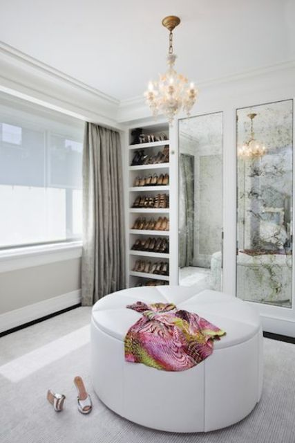 a refined modern closet in neutrals, with open show shelves, vintage mirrors, a white round pouf and a lovely chandelier