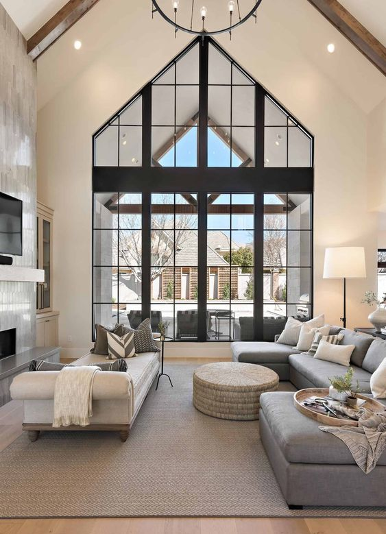 a refined modern living room with double-height windows, a fireplace clad with tiles, a grey sectional, white daybed and a round pouf