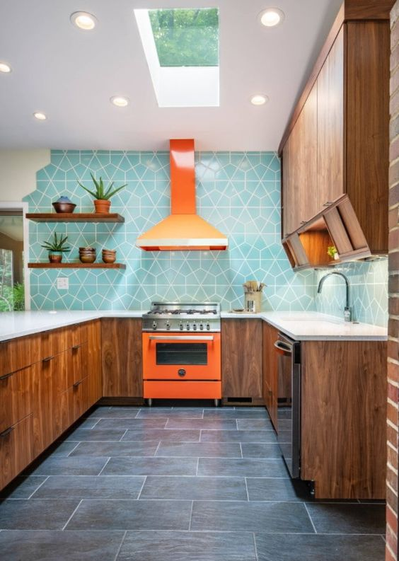 a rich-stained modern kitchen with white countertops, a bold orange cooker and a hood and a bright blue geo tile backsplash