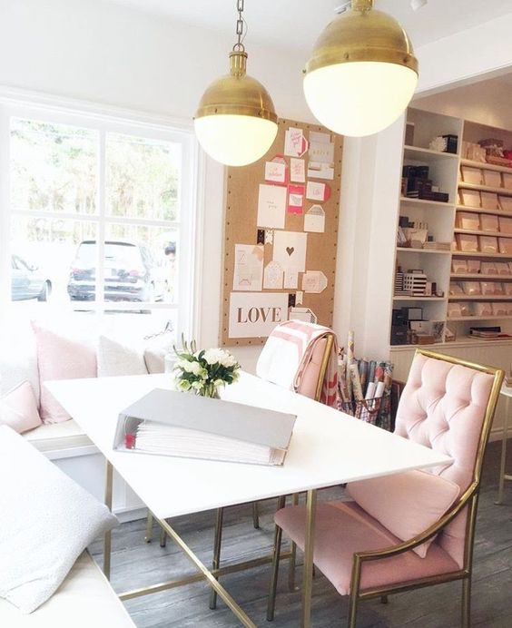 a romantic home office with an L-shaped bench, blush chairs, gold pendant lamps and a mood board