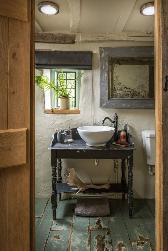 a shabby chic barn bathroom with white plaster walls, vintage furniture, a shabby floor and some greenery to refresh the space