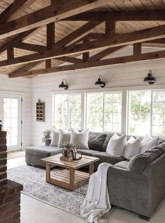 a simple barn living room with white planked walls, a grey sofa, wooden beams, a wooden table and lots of natural light