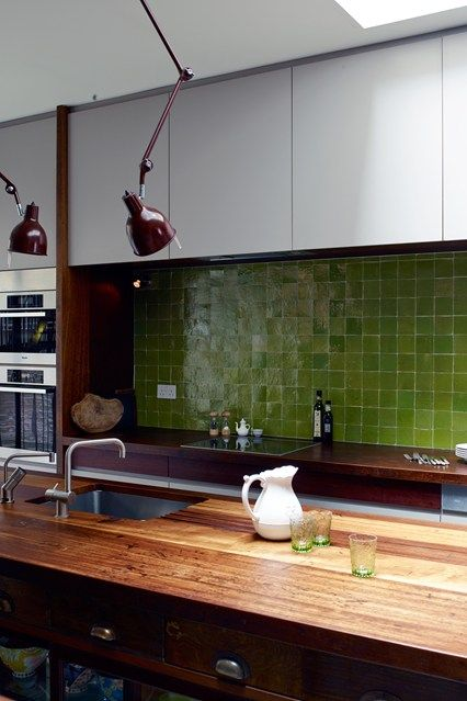 a sleek white kitchen with rich-stained butcherblock countertops, a wooden vintage sideboard kitchen island, a bold green tile backsplash