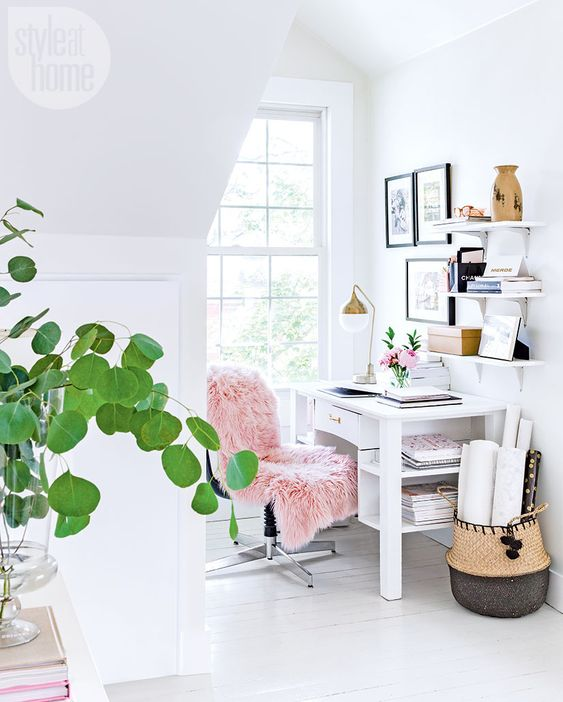 a small airy home office with a comfy desk and chair, some shelves, a basket and a gallery wall
