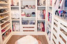 a small and glam closet with open shelves and storage units, drawers with mirror fronts, a pink rug and a faux fur stool is cool