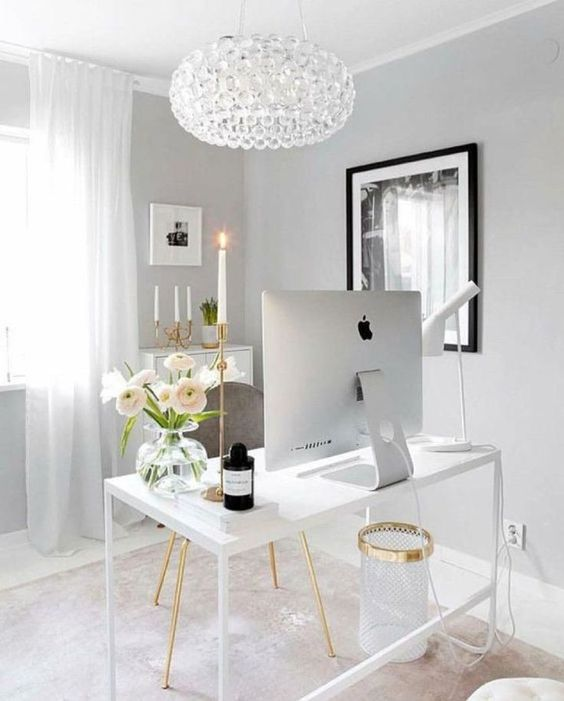a sophisticated feminine home office with white and grey furniture, a crystal chandelier and touches of gold