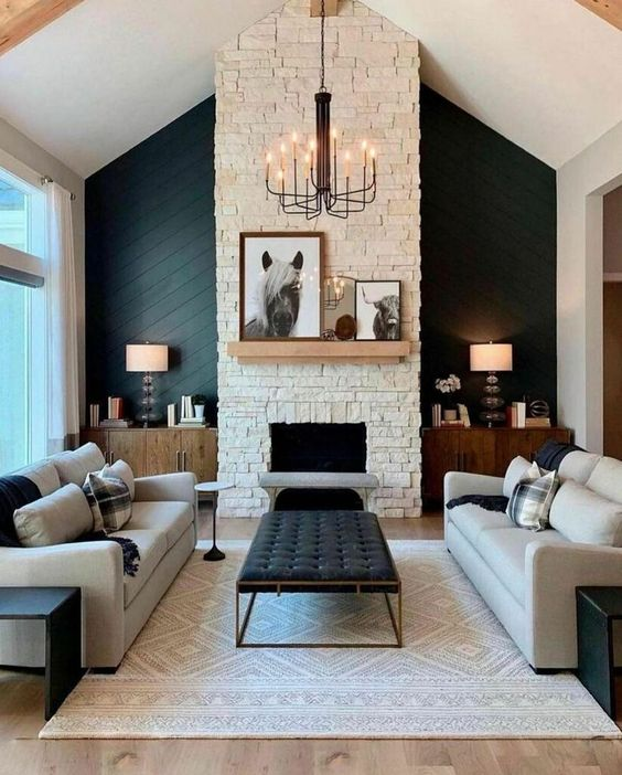 a sophisticated modern barn living room with a fireplace clad with faux stone, neutral seating furniture, a printed rug, a black ottoman, table lamps and a chic chandelier
