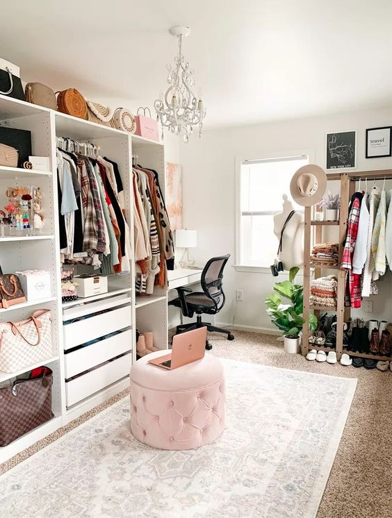 a stylish cloffice with open storage units, drawers and an open storage rack, a pink pouf, a white desk and a crystal chandelier