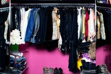 a super bold and glam closet in purple, hot pink and black, with a gold chandelier, acrylic storage shelves and an open clothes rack