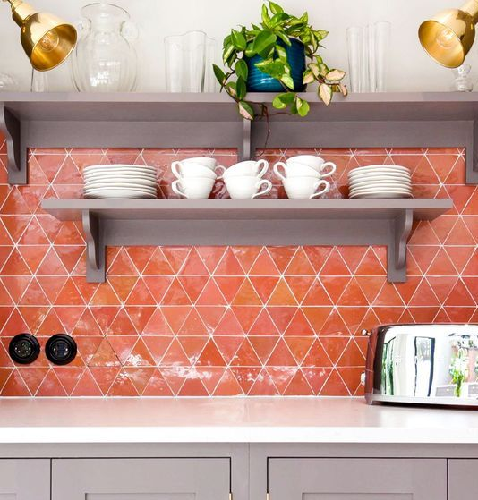 a super bold orange geo tile backsplash is a bold solution for a modern kitchen, it will add much color to the space