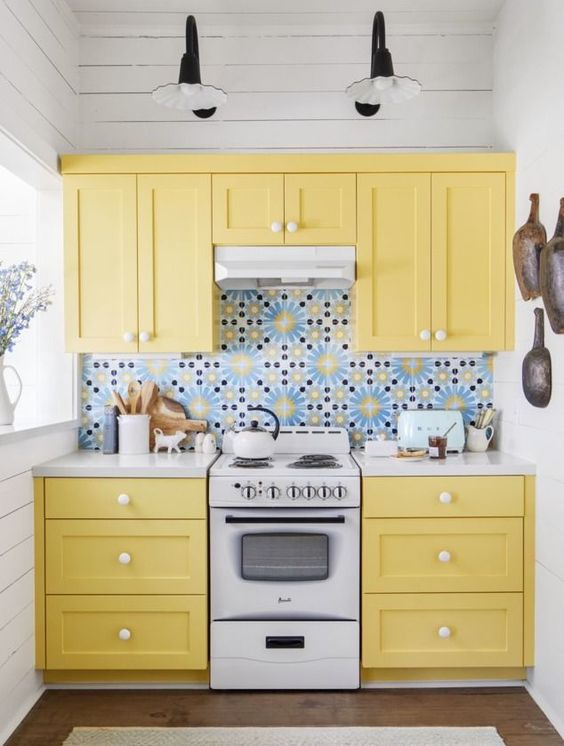 a tiny yellow kitchen with shaker cabinets, a bold blue patterned tile backsplash is a cheerful and fun space to be in