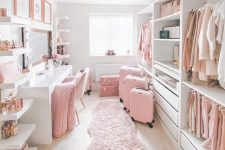 a very girlish closed with open storage units and drawers, with open selves, a white vanity with a large mirror and pink touches
