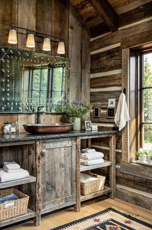 a vintage barn bathroom fully clad with reclaimed and weathered wood, with a catchy mirror, a chandelier and a wooden vanity