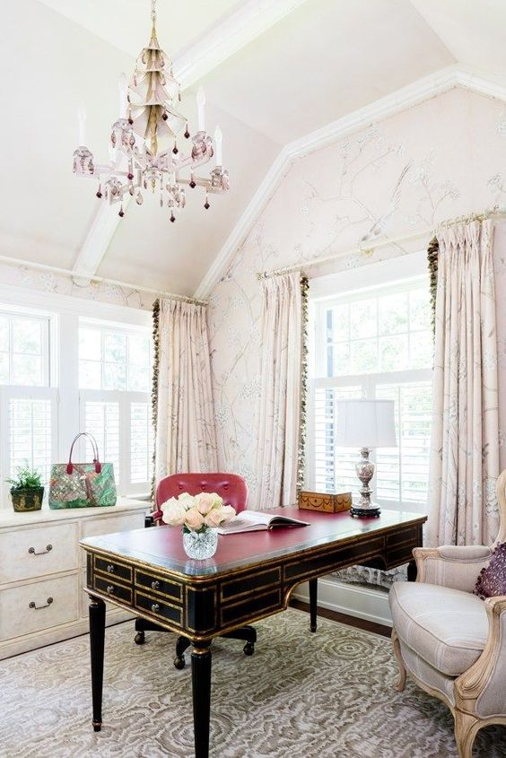 a welcoming and elegant feminine home office with blush floral walls and curtains, a refined black and gold desk, a lilac and pink chandelier and a chic chair