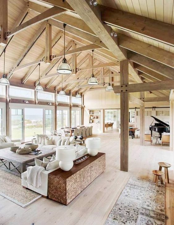 a welcoming barn living room with a stained wooden ceiling and beams and pillars, neutral seating furniture, wooden furniture items and a piano